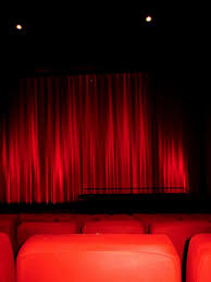 image of red curtain and plush seats in movie theatre
